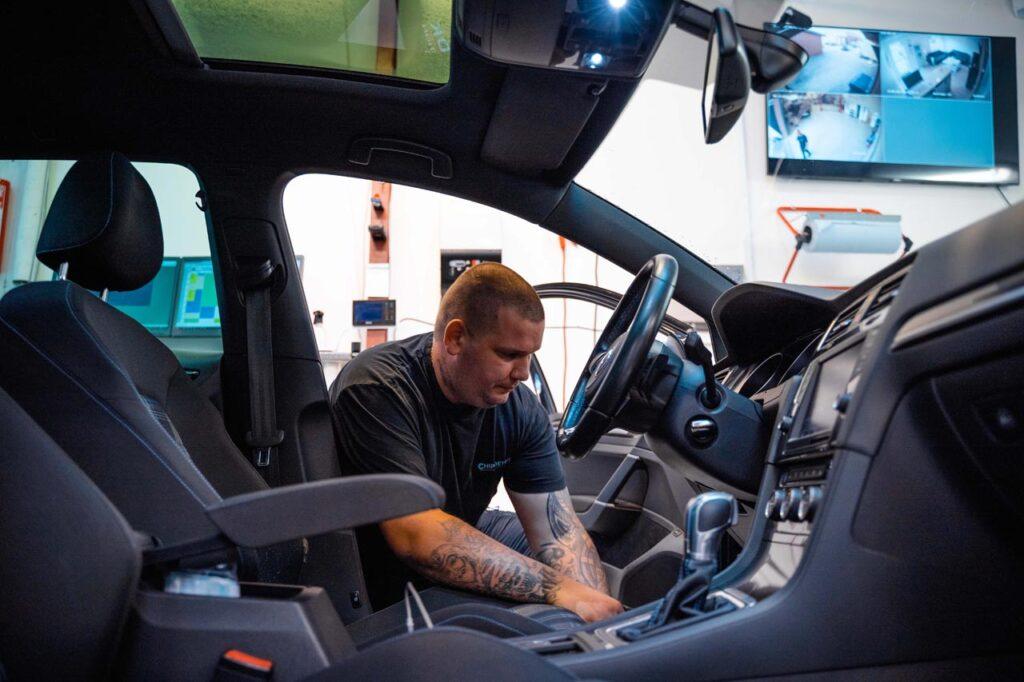 En mekaniker, med en sort t-shirt hvor der står chip-det.dk, som er ved at chiptuning en bil